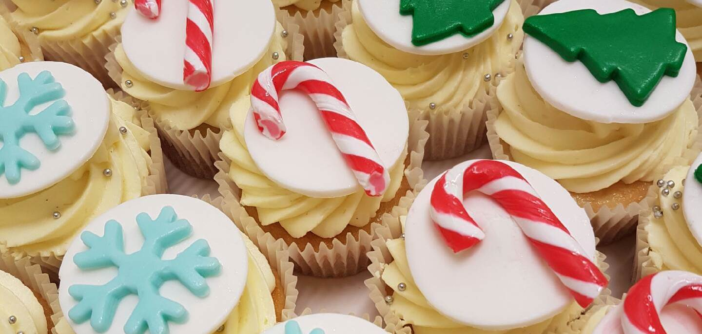A close up shot of Christmas mini cakes from Chez Nous Corporate Catering. Includes candy canes, christmas trees and snow flakes.