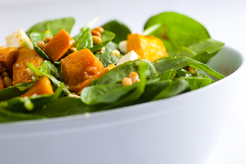 A bowl of Chez Nous Corporate's baby spinach and roasted pumpkin salad
